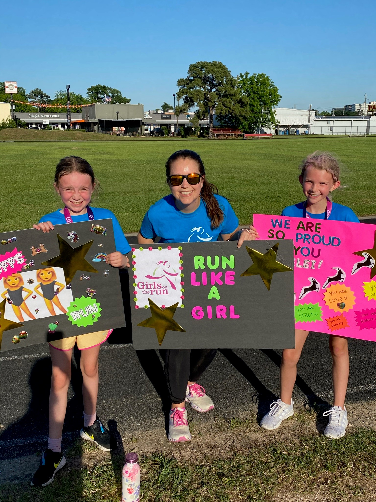 Girls on the Run Coach and participants standing outdoors, each holding a handmade sign. The signs have power poses, positive affirmation statements and words of support.