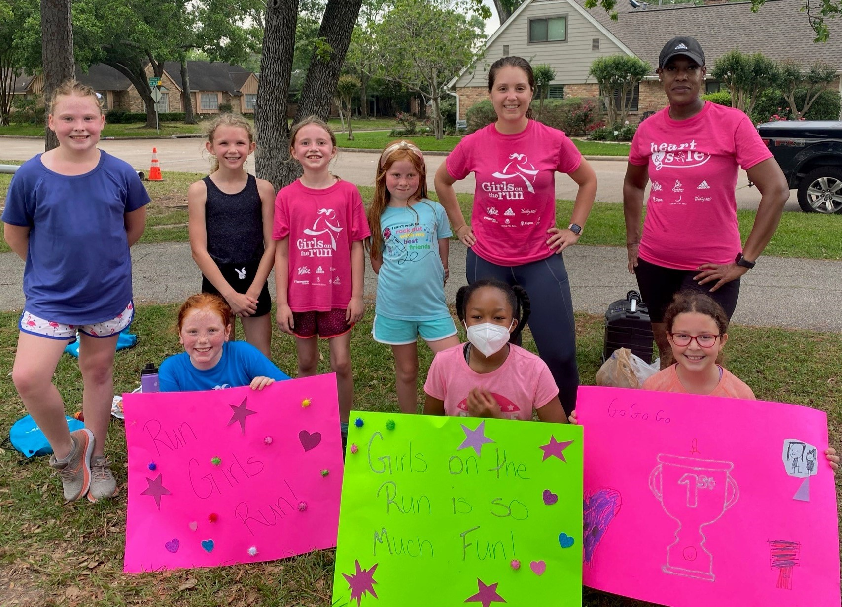 """Girls on the Run coaches and teammates grouped together holding signs with positive affirmations about GOTR. They read: """"Girls on the Run is so much fun!"""" and """"Go, go, go!"""" Great reminders that no matter our pathway, we can support each other."""