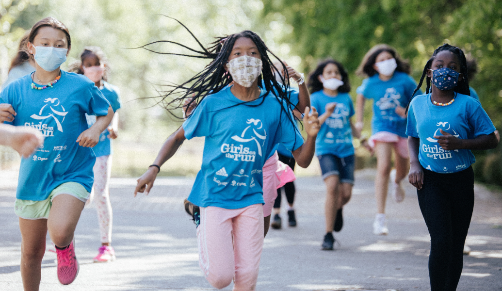 Girls on the Run participants running outside. They are wearing GOTR program shirts. Each girl is unique. The image indicates diversity in culture, ethnicity and accessibility, which shows how the program is welcoming and truly celebrates global diversity awareness.